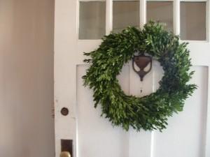 An evergreen wreath on a white door